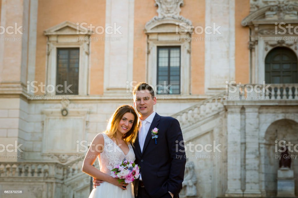 Bride and groom wedding poses in front of Capitol Hill (Campidoglio), Rome, Italy foto stock royalty-free