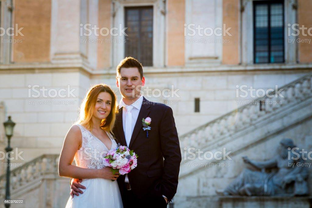 Bruden och brudgummen bröllop poser framför Capitol Hill (Campidoglio), Rom, Italien royaltyfri bildbanksbilder