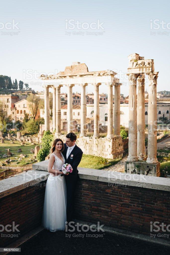 Bruden och brudgummen bröllop poser framför Roman Forum, Rom, Italien royaltyfri bildbanksbilder