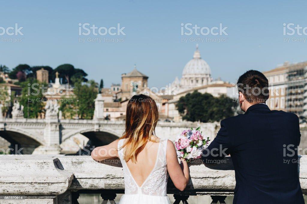 花嫁および新郎結婚式ポーズ見ているサン ・ ピエトロ大聖堂、ローマ、イタリアのテヴェレ川のほとり ロイヤリティフリーストックフォト