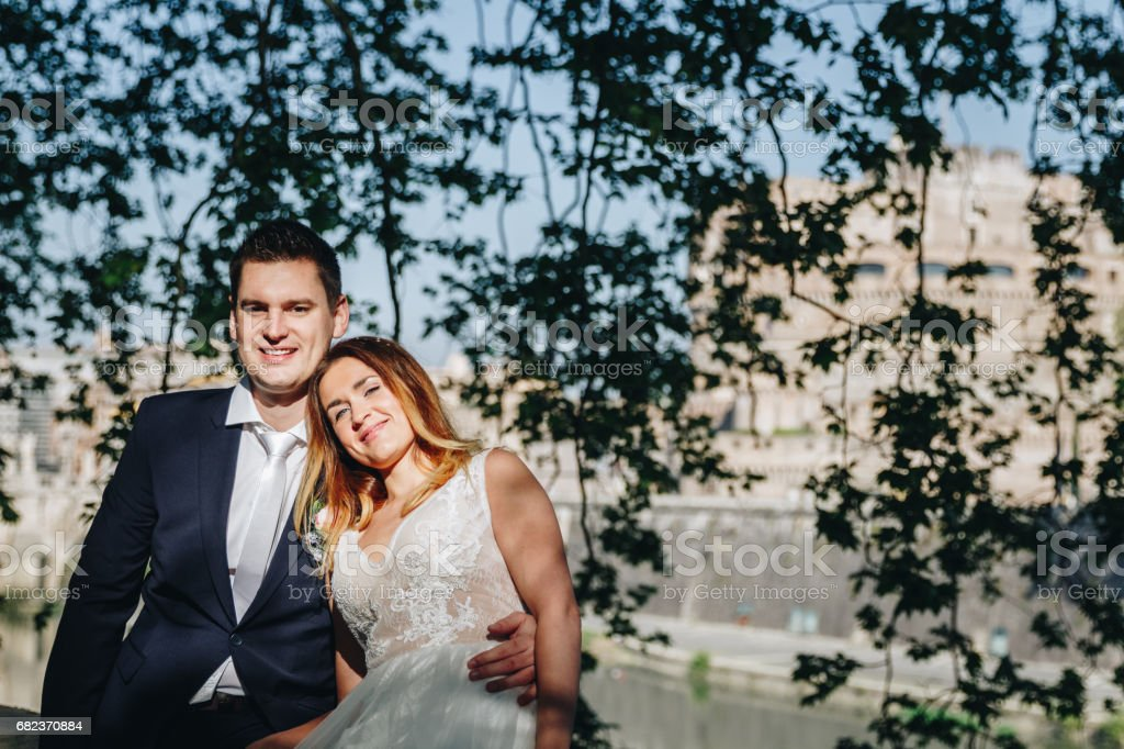Bride and groom wedding poses under trees on the bank of the river Tiber, Rome, Italy zbiór zdjęć royalty-free