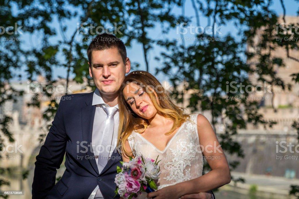 Bruden och brudgummen bröllop poser under träd på stranden av floden Tibern, Rom, Italien royaltyfri bildbanksbilder