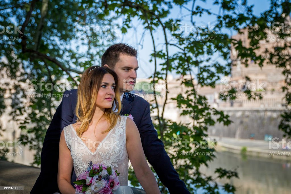 Bride and groom wedding poses under trees on the bank of the river Tiber, Rome, Italy royalty-free stock photo