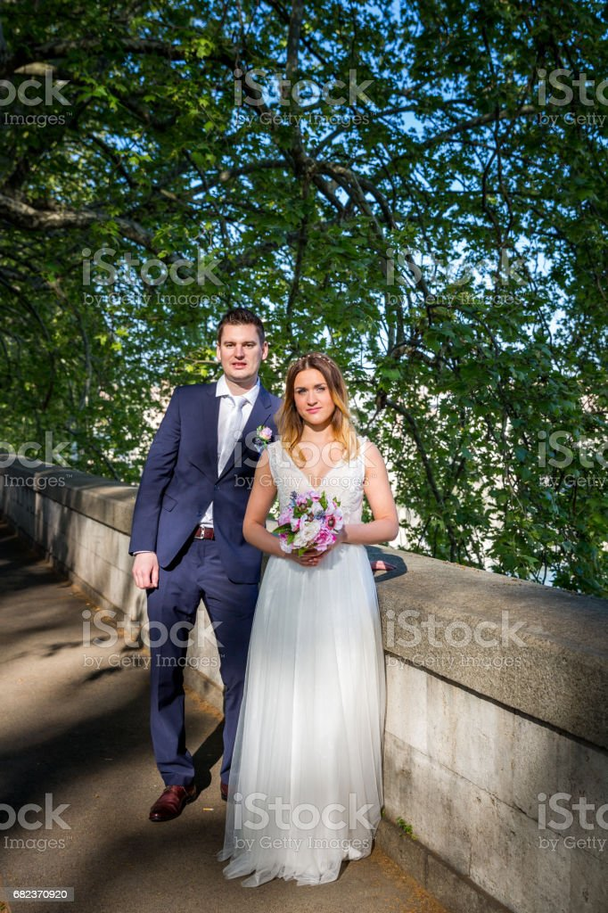Bride and groom wedding poses under trees on the bank of the river Tiber, Rome, Italy foto stock royalty-free
