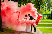 Bride and groom with a bright red smoke