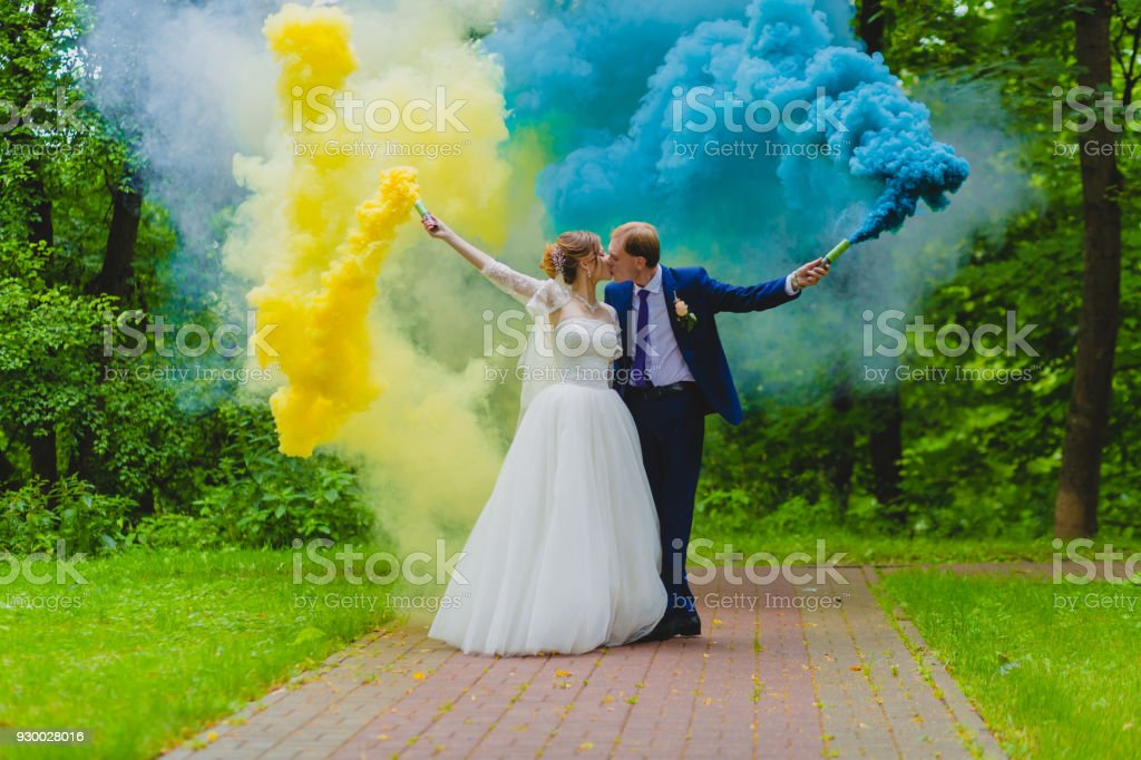 Bride and groom with colorful smoke bombs stock photo