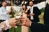 Close up of new married couple toasting champagne glasses at wedding party. Bride and groom hands clinking glasses at wedding reception.