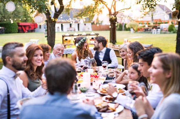 braut und bräutigam mit gästen bei hochzeitsfeier draußen im hinterhof. - bräutigam tisch stock-fotos und bilder