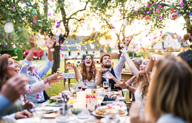 Bride and groom with guests at wedding reception outside in the backyard. stock photo