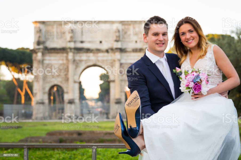 Bride and groom with 'Just Married' written on shoe soles, Rome cityscape in the background, Italy. Selective focus. zbiór zdjęć royalty-free