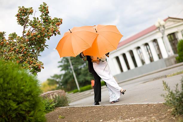 Braut und Bräutigam mit orange Regenschirm – Foto