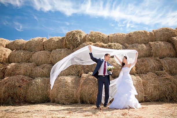 Braut und Bräutigam mit Schleier in der Nähe von Heu – Foto
