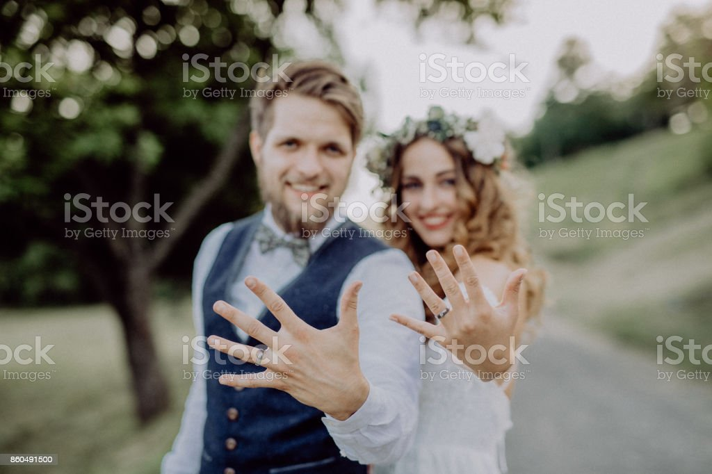 Bride and groom with wedding rings in nature. stock photo
