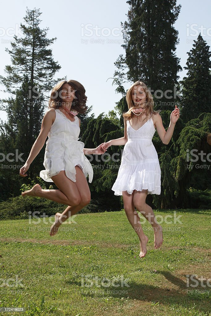 Bride and her friend jumping royalty-free stock photo