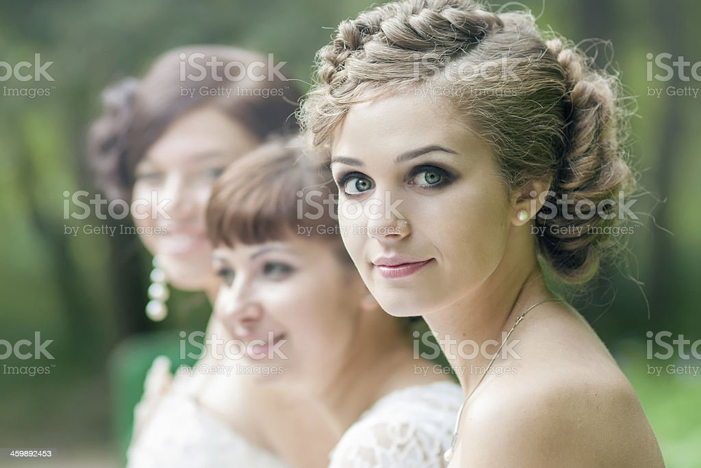 Bride and two friends dressed in white with hair done stock photo