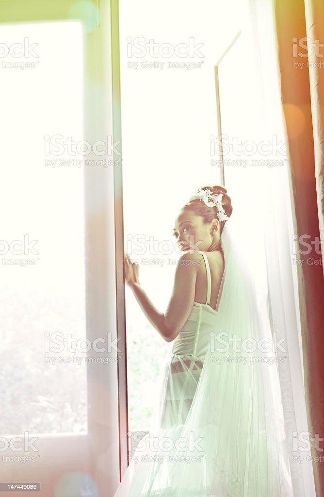 Bride at balcony, sunset royalty-free stock photo