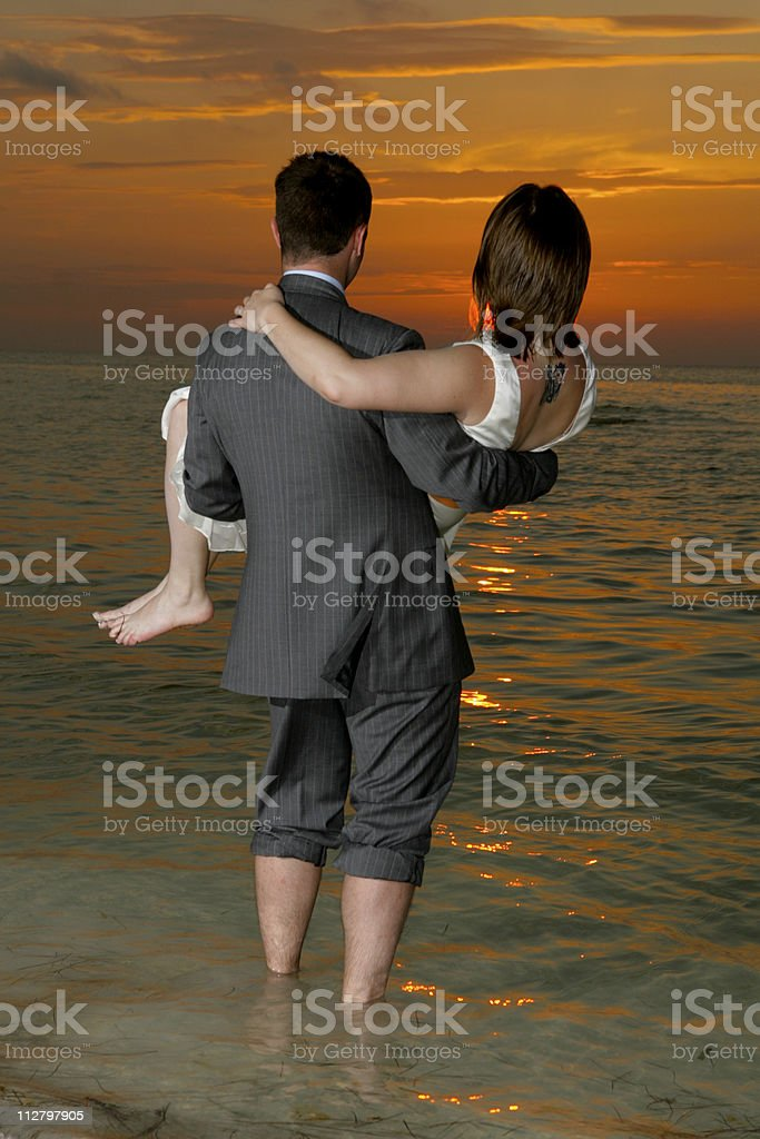 Bride being embraced by Groom at Mexico coean sunset wedding. royalty-free stock photo
