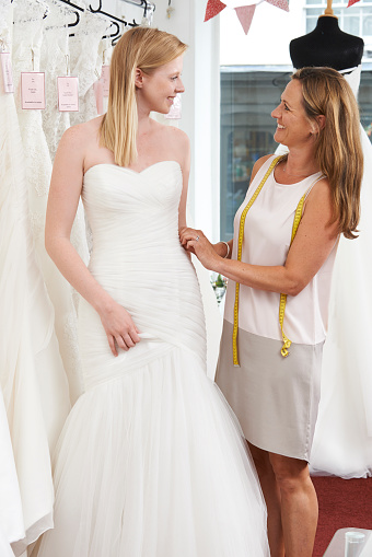istock Bride Being Fitted For Wedding Dress By Store Owner 483288592