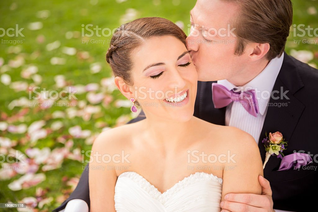 Bride being kissed by the groom royalty-free stock photo