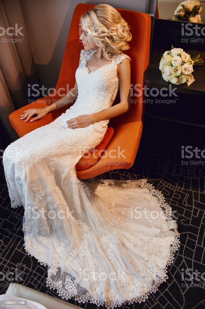 Bride Blonde In White Wedding Dress Sitting In A Chair In A Hotel Room Woman Resting Before The Wedding Ceremony Tired Bride Sitting With A Bouquet Of Flowers Stock Photo Download,Fashionable Maria B Fashionable Wedding Dresses For Girls 2020