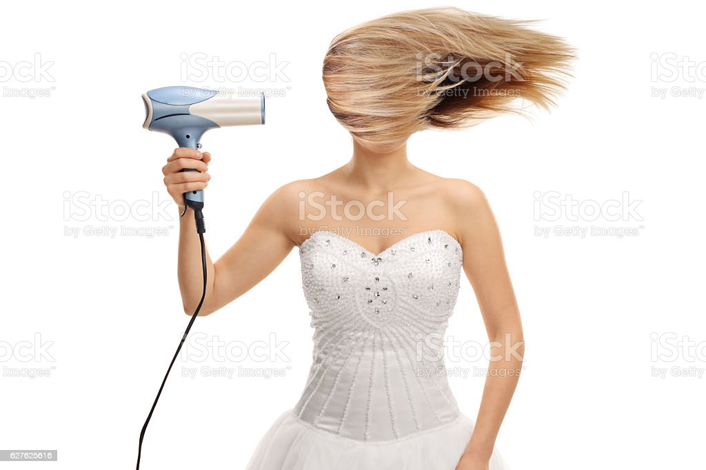 Bride blowing her hair with a hair dryer stock photo