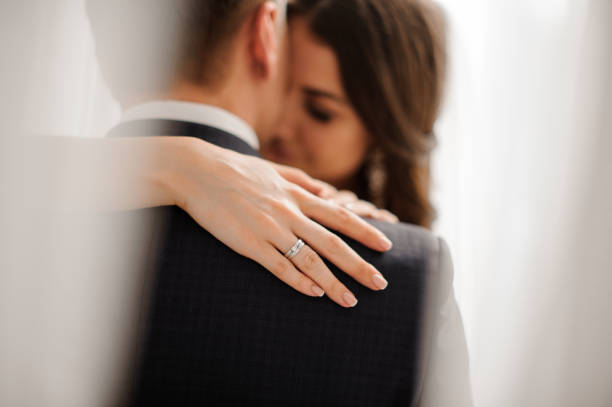 bride demonstrates her elegant diamond engagement ring handsome bride brunette demonstrates her elegant diamond engagement ring on the bride's shoulder on a white background bridegroom stock pictures, royalty-free photos & images