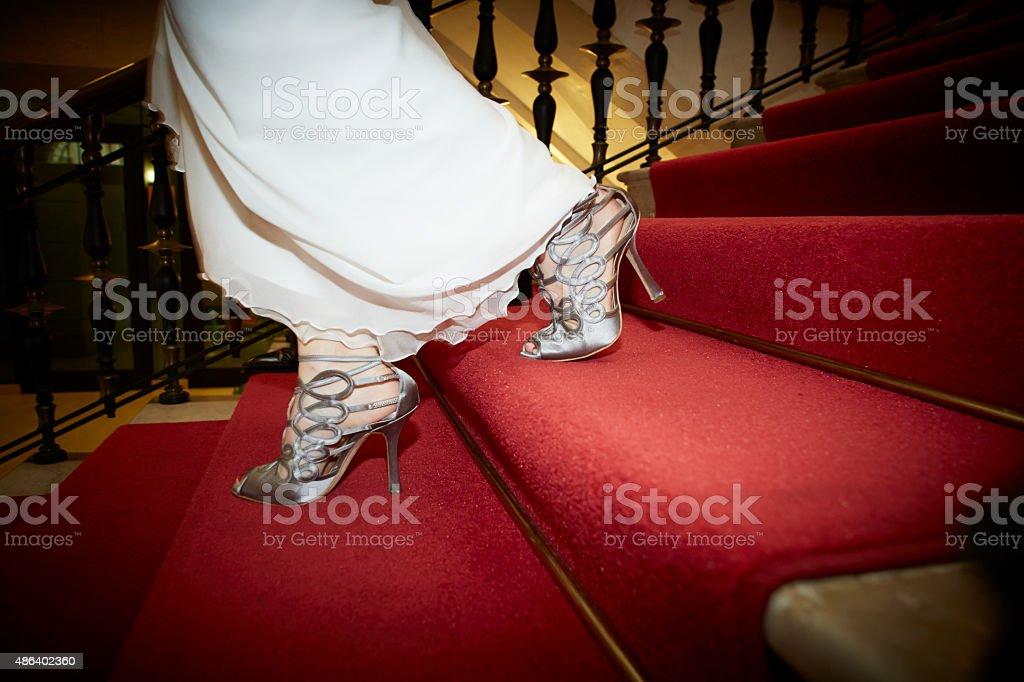 Novia bajando una escalera con alfombra roja - foto de stock