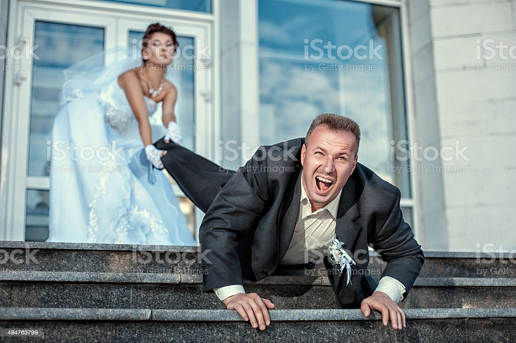 Bride dragging groom at the wedding. stock photo
