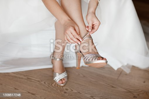 Bride dresses shoes before the wedding ceremony. bride morning. Closeup detail of bride putting on high heeled sandal wedding shoes. Wedding bride shoes. Beautiful legs.