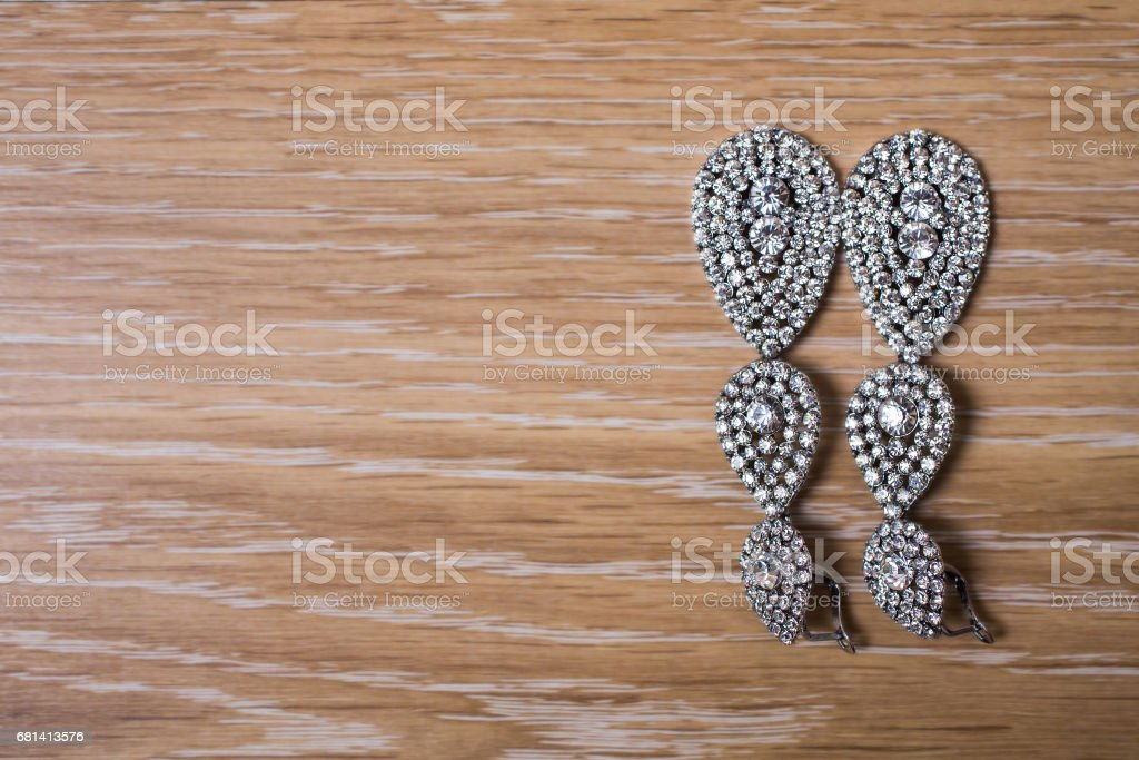 Bride earrings on a wooden background, preparation for the wedding royalty-free stock photo