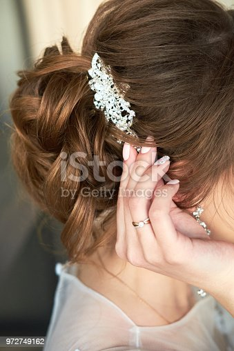 bride fastens the barrette in her hair, close up