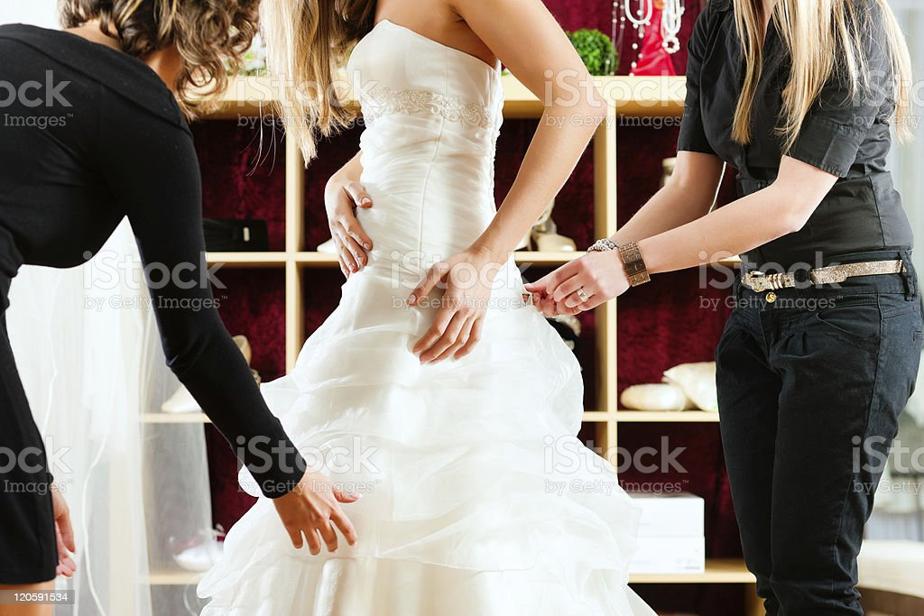 A bride fitting her wedding dress in the shop Bride at the clothes shop for wedding dresses; she is choosing a dress and the designer are assisting her Adult Stock Photo