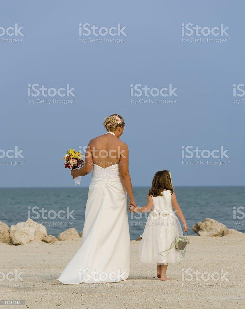 Bride & Flower Girl Walk on the Beach royalty-free stock photo