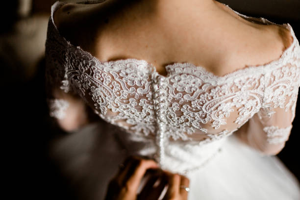 Bride from the back. Bride from the back. Bridesmaid zips the wedding dress. corset stock pictures, royalty-free photos & images