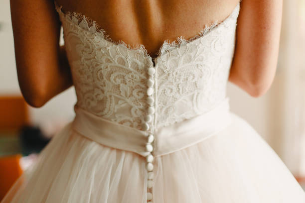 Bride getting ready, they help her by buttoning the buttons on the back of her dress. Bride getting ready, they help her by buttoning the buttons on the back of her dress. corset stock pictures, royalty-free photos & images