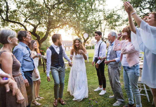 Bride, groom and guests at wedding reception outside in the backyard. Bride, groom and their guests at the wedding reception outside in the backyard. Family celebration. guest stock pictures, royalty-free photos & images