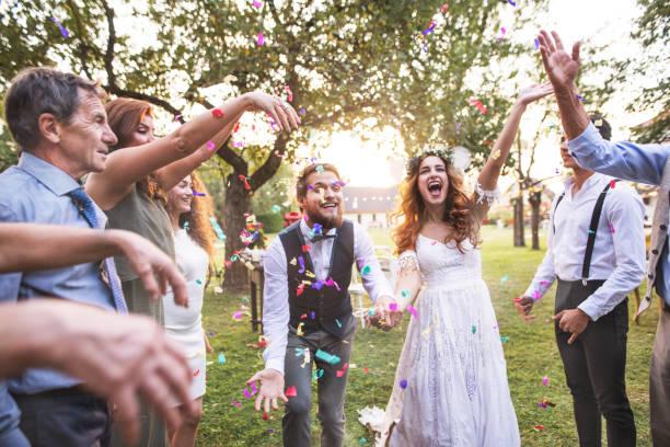 braut, bräutigam und gäste werfen konfetti auf hochzeit außerhalb. - mütterbrautkleider stock-fotos und bilder