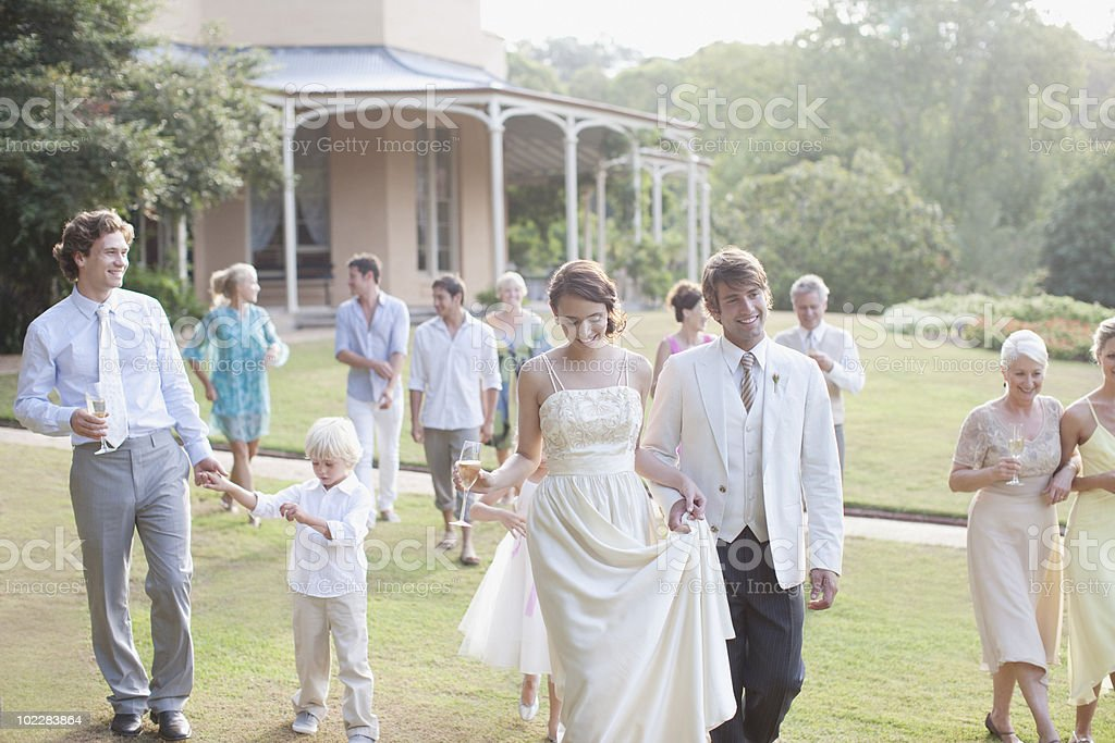 Bride, groom and guests walking across lawn royalty-free stock photo