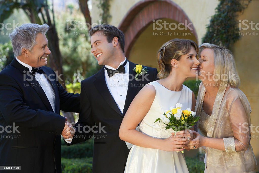 Bride, groom and parents exchanging wishes stock photo
