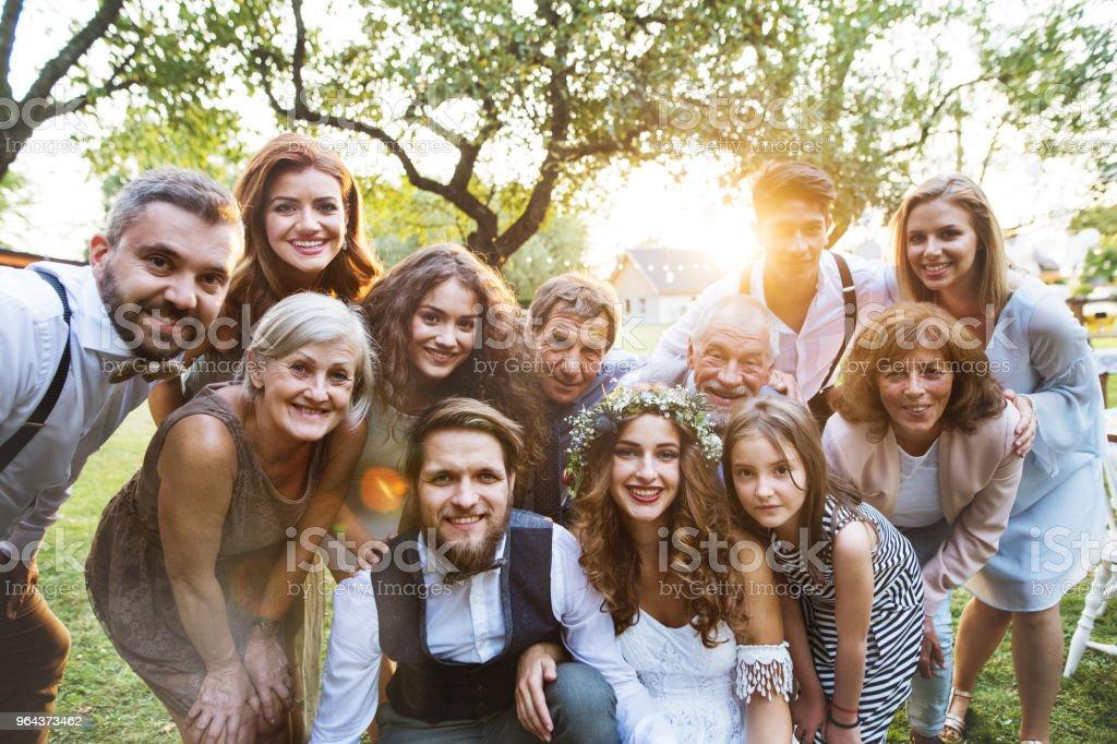 Bruid, bruidegom, gasten poseren voor de foto bij de bruiloft receptie buiten in de achtertuin. - Royalty-free 20-29 jaar Stockfoto