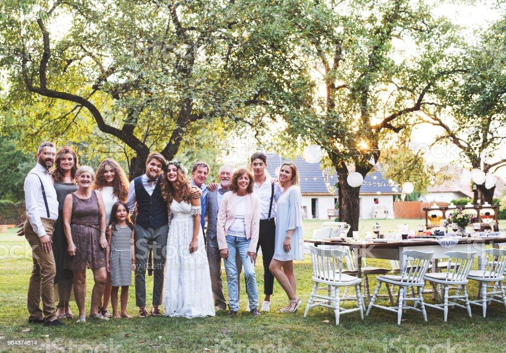 Noiva, noivo, convidados a posar para a foto na festa de casamento lá fora no quintal. - Foto de stock de 20 Anos royalty-free