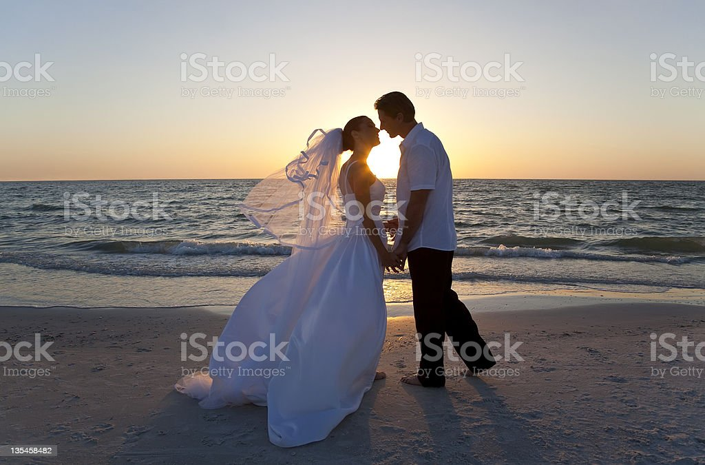 Bride & Groom Married Couple Kissing Sunset Beach Wedding stock photo