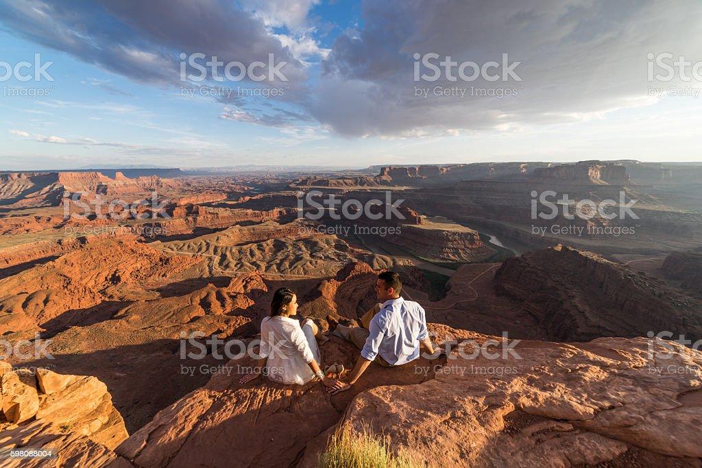 Bride & groom posing over vast canyons.  Utah desert, Moab. stock photo