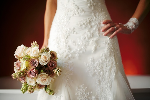 Bride hand on hip with bouquet