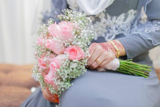 main de la mariée avec le henné et un bouquet de fleur. - mariage musulman photos et images de collection