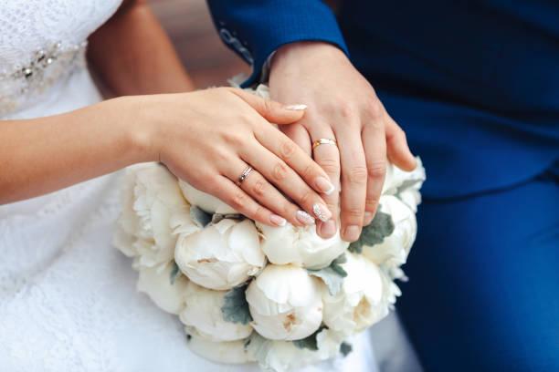 hände der braut mit ring und hochzeit blumenstrauß - heiratsantragsring stock-fotos und bilder