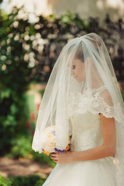 bride hidden by a veil for a walk in the park - veil stock pictures, royalty-free photos & images