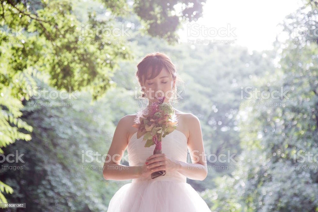 Bride holding a bouquet in the park stock photo