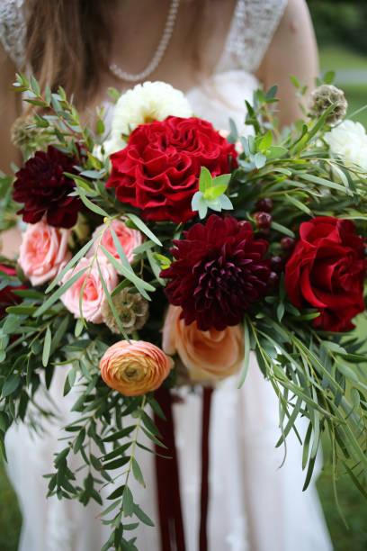 Bride holding a bouquet of red maroon pink peach and yellow flowers picture id1045501510?b=1&k=6&m=1045501510&s=612x612&w=0&h= 7qj6roq6k39jnlf ebqnhrdlpqtqzslpz6jvdguu90=