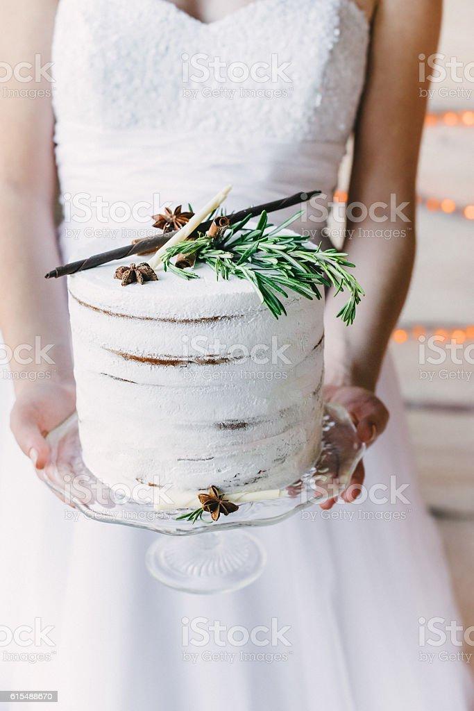 bride holding a craft cake on a glass stand - foto de acervo
